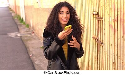 Young Arab woman walking in the street using her smartphone