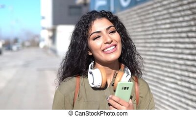 Young Arab Woman walking in the street with headphones and ...