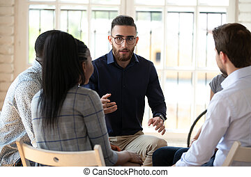 Young arabian male employee sitting in circle with colleagues.