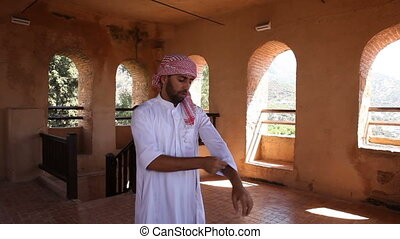 Young arabian man in traditional clothes rolls up sleeves in...