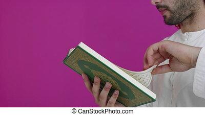 Arabian Muslim man in traditional clothes praying reading Quran Islamic holy book