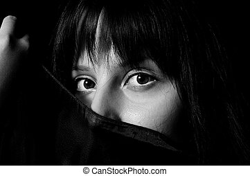 Young arabic girl hiding her face with a scarf in black and white