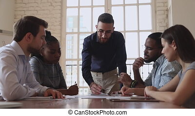 Focused young arabic male team leader boss in eyeglasses listening to ideas of mixed race colleagues, discussing project details together in brainstorming meeting at international company office.