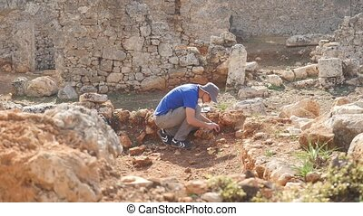 Young archeologist works on an archaeological site in the...