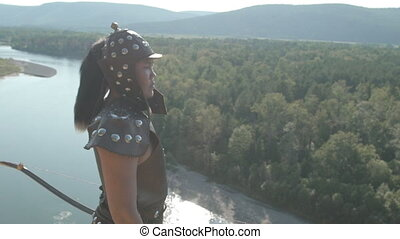 Young archer stands on high mountain on sunny day. Warrior...