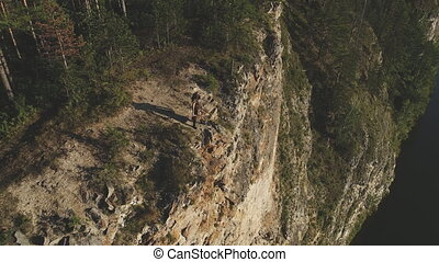 Young archer stands on rock cliff on sunny day. Bowman...