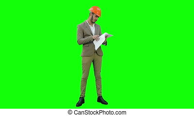 Young architect in helmet checking construction plans on a Green Screen, Chroma Key.
