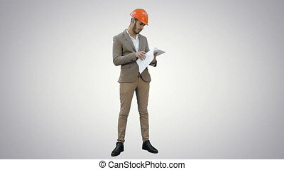 Young architect in helmet checking construction plans on white background.