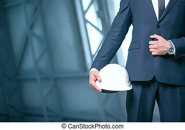 Young architect in suit is carrying a hardhat