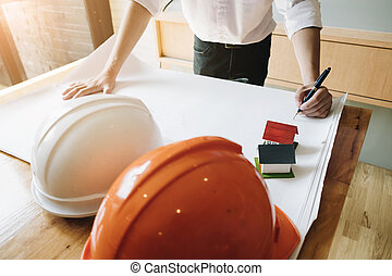 Young Architect Male Freehand Drawing, Civil engineer sketching a blueprint of construction project with small house model and safety helmet in office, Construction Concept.