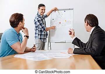 Young architect pointing at the printout on whiteboard