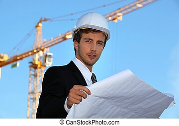 Young architect with plans on-site