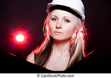 Young architect woman construction worker reading blueprints