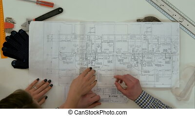 Young architects working on blueprints