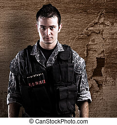 young armed soldier against a grunge background