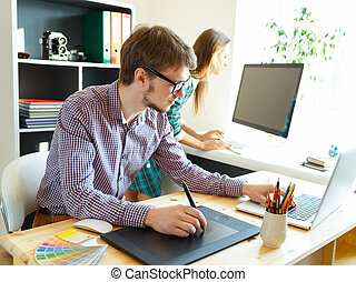 Young artist drawing something on graphic tablet at the office