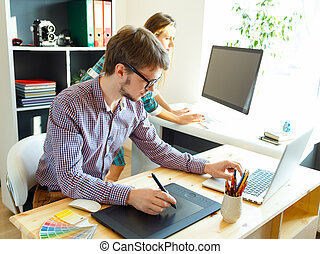 Young artist drawing something on graphic tablet