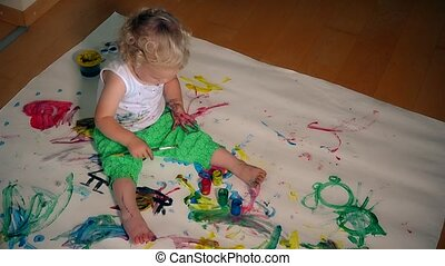 young artist kid girl painting on her hand and white paper on floor