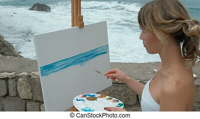 Young artist on the shore of the surging waves in writing seascape.