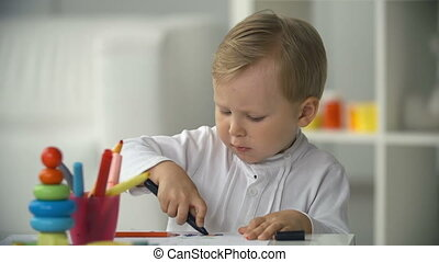 Young Artist - Portrait of boy drawing at the table