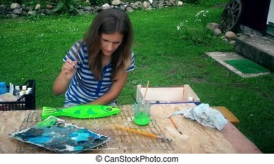 Young artist woman painting fish decoration on wooden table in house yard