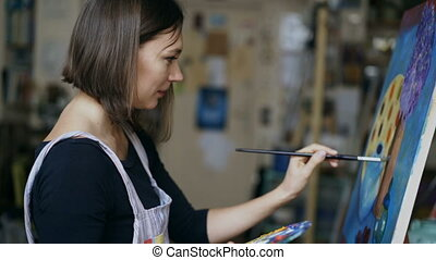 Young artist woman painting still life picture on canvas in art-school