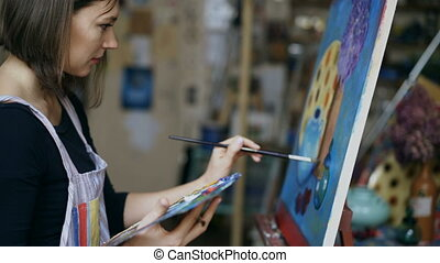 Young artist woman painting still life picture on canvas in...