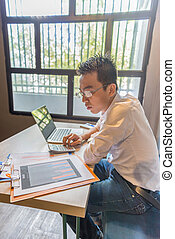 Young Asian accountant working on financial business documents