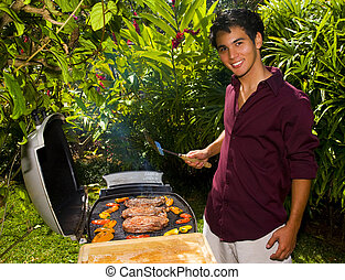 young Asian American man grilling beef steaks on a bar-b-que in his yard