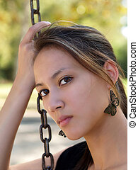 Young asian american woman holding chain from swing