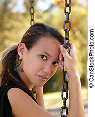Young asian american woman on swing chains