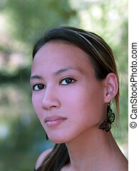 Young asian american woman outdoor portrait leaves