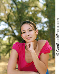Young asian american woman portrait outdoors pink top