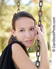 Young asian american woman sitting on swing