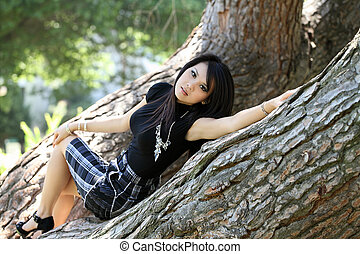Young Asian American Woman Skirt reclining in tree