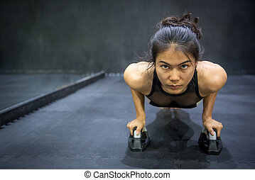 Young Asian athlete woman doing push up on the floor