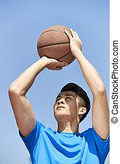 young asian basketball player making jump shot - young asian...