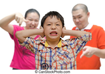 boy covering ears while parents scold him