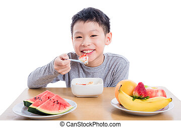 boy eating cereal with yogurt for breakfast over white background