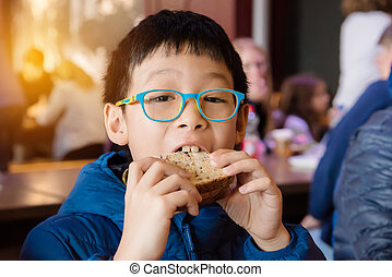 boy eating sandwich for lunch