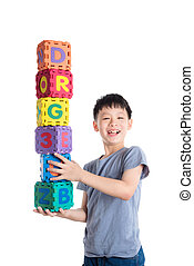 Young asian boy holding alphabet blocks over white background
