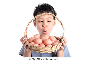 Young asian boy holding eggs basket over white background