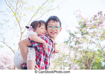 boy holding his sister on back