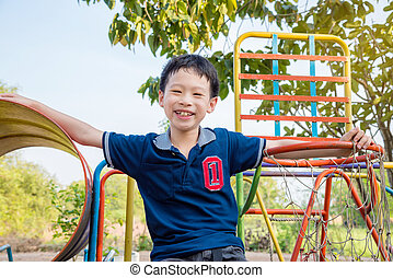 Young asian boy playing at playground