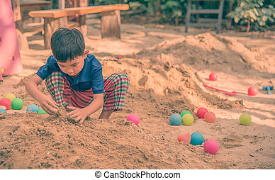 young asian boy playing in sand pit.