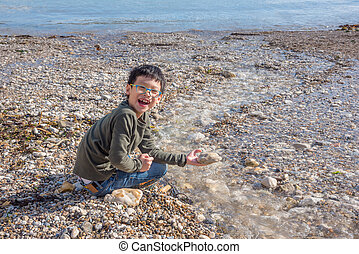 Young Asian boy playing on the beach