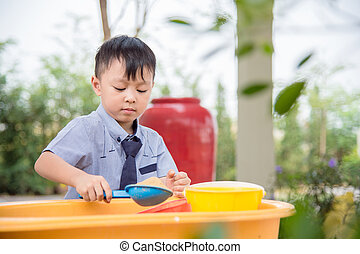 Young asian boy playing sand in sandbox