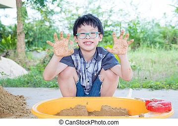 boy playing sand in sandbox