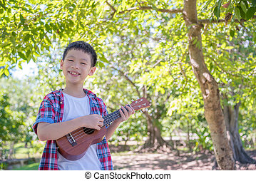 boy playing ukulele in park