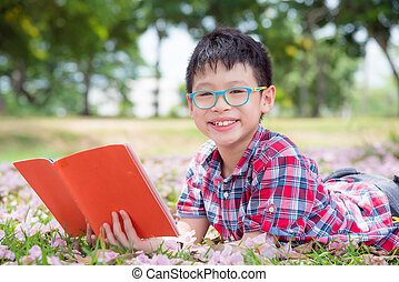 boy reading book in park